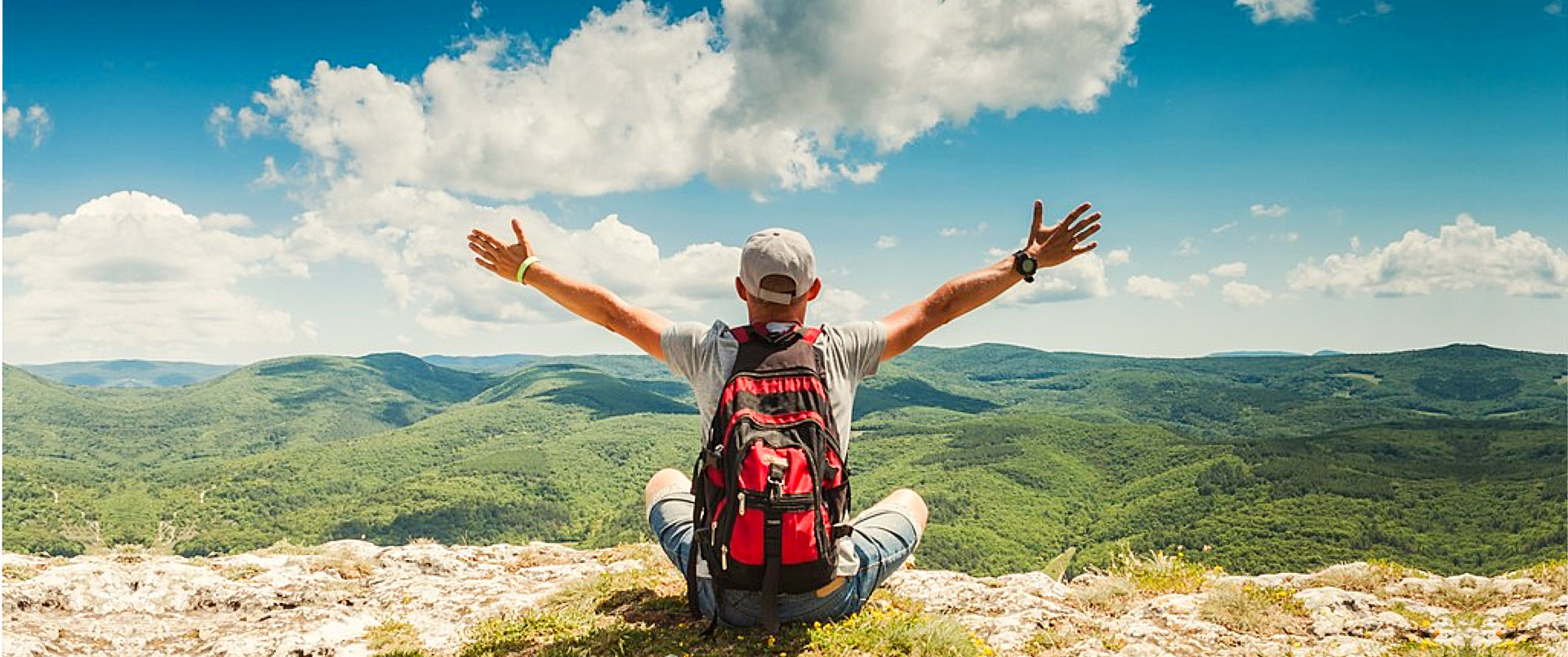 man raising his arms while looking at a mountain view