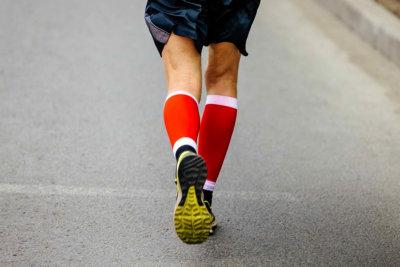back feet men runner in red compression socks running street